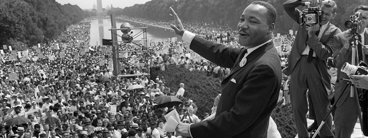 Martin Luther King, Jr. waves to supporters from the steps of th
